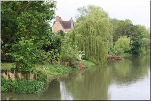 A quiet spot in Bedfordshire for farm holidays with a house, willow tree and river
