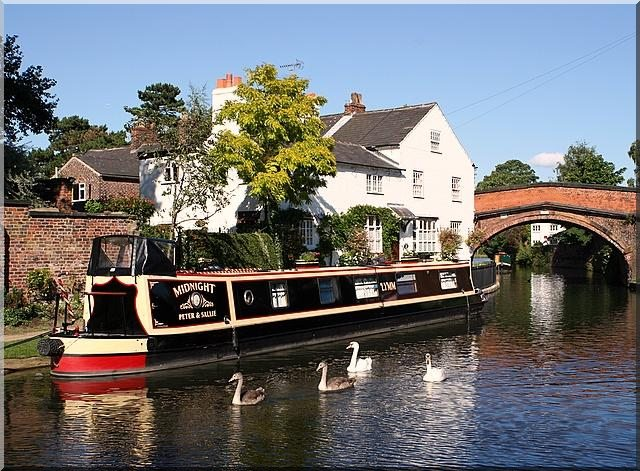 A narrowboat on a river in Cheshire