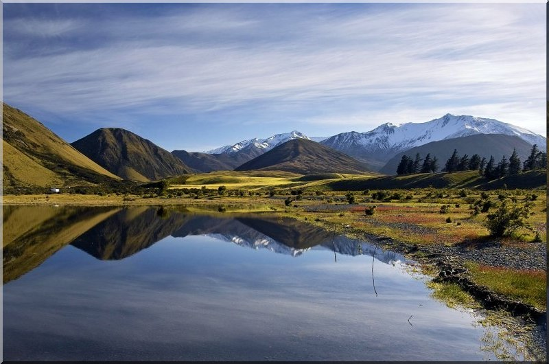 canterbury new zealand with a lagoon and the mountains reflected in the water