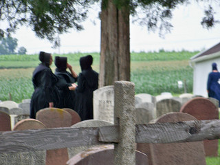 3 Amish women dressed in black at an Amish funeral