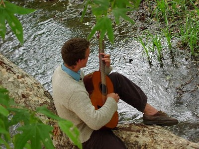 A man sitting down at a river playing a guitar.