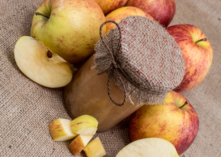 apples surrounding a bottle of apple sauce with a jute cover.