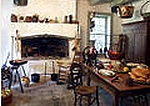 A colonial country kichen with fireplace and utensils.