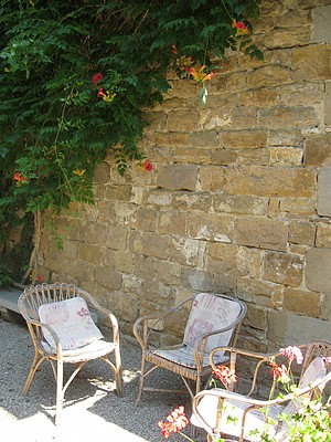 3 chairs in a country garden alongside a stone wall