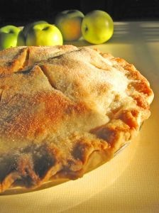 A freshly baked country apple pie with apples on the side.