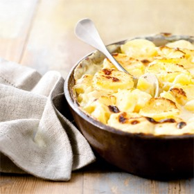 a bowl of creamy layered potato bake