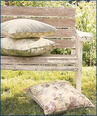An old cottage bench with some printed cushions