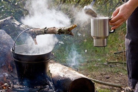 pouring water from a campfire bucket for tea