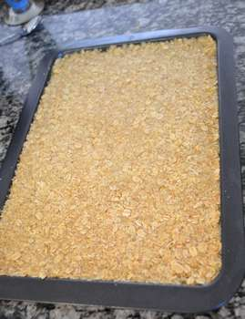 Oat mixture well flattened in baking tray.