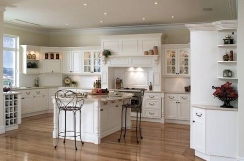 A French Country Kitchen With White Cupboards And Wooden Floors.