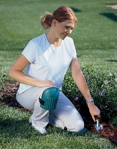 A lady kneeling in the garden using knee pads.