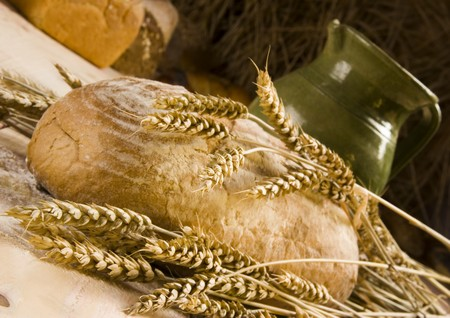 a round loaf of homemade bread with sheaves of wheat and a green jug on a wooden table