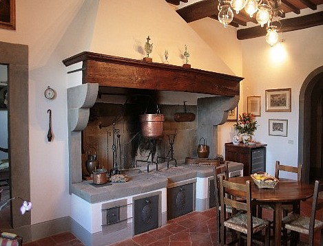 A traditional Italian kitchen with a fireplace for cooking.