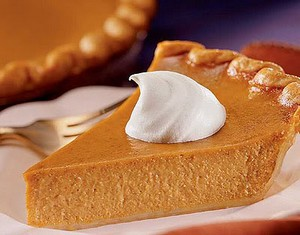 A slice of luxury pumpkin pie with cream.
