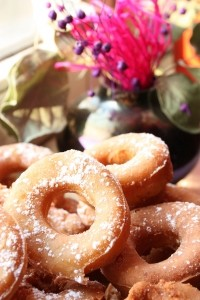 Maple donuts in a pile on a plate.