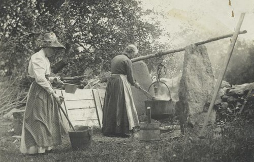 2 women making soap the old fashioned way over an open fire