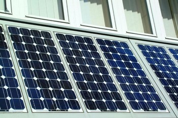 A panel of photovoltaic cells on the side of a building