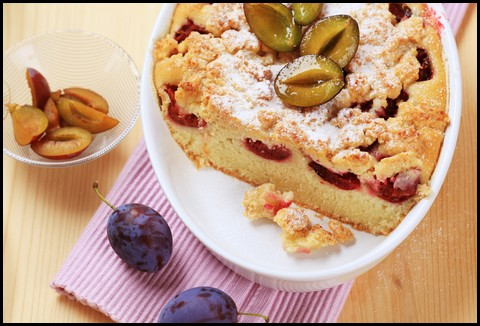 a plum cake decorated with sliced, fresh plums