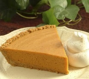 A wedge of pumpkin butterscotch pie on a plate with cream.