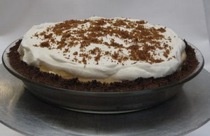 Pumpkin chiffon pie with cream and cinnamon.