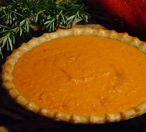 Pumpkin pie in a pie shell with rosemary on the side.