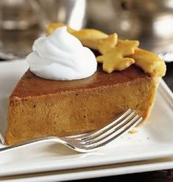 A wedge of pumpkin pie topped with cream.