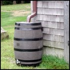 A wooden barrel catching rain water.