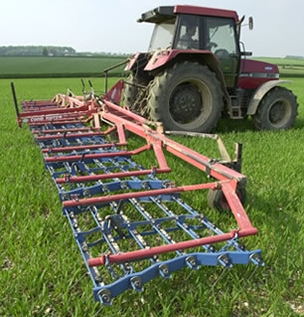 A tined weeder comb harrow being pulled by a tractor.
