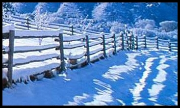 A winter scene with snow and a farm fence