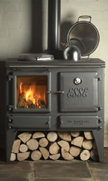 a black Esse woodstove with chopped wood on the floor