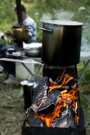 a steaming pot cooking over a camp fire