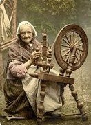 An old lady at a spinning wheel