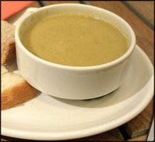 a bowl of courgette soup with crusty bread
