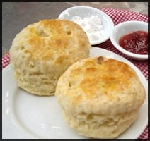 2 scones on a plate with cream and jam